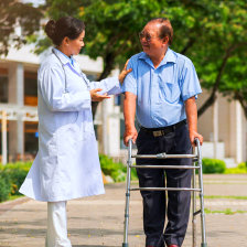nurse talking to senior man on walker