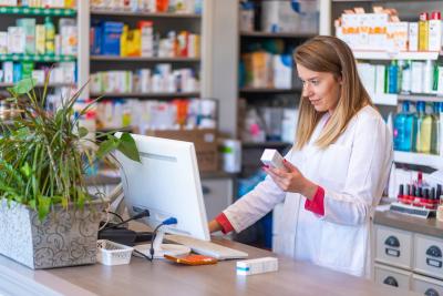 female pharmacist working in chemist shop or pharmacy
