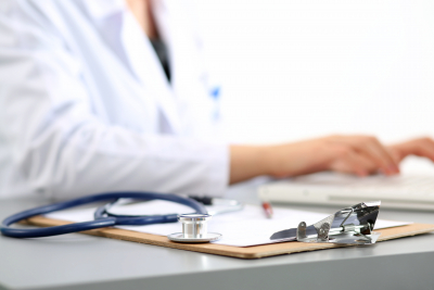 doctor typing something on background with a stethoscope