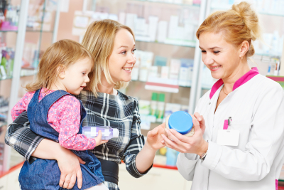pharmacist woman demonstrating vitamin to child girl with mother in pharmacy drugstore