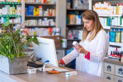 female pharmacist working in chemist shop or pharmacy